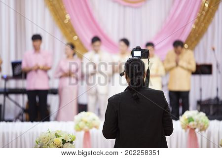 Cameraman recording video of Wedding out of focusblur background. poster