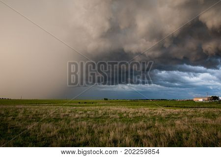 A severe thunderstorm with a dense hailshaft moves over northern Oklahoma farmland