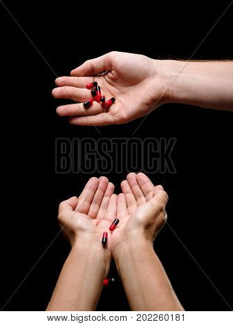 Palms holding red and black capsules of vitamins on a black background. Prescripted drugs in capsules. Antibiotics and painkillers in tablets. Medical treatment, healthcare and pharmaceutical therapy.