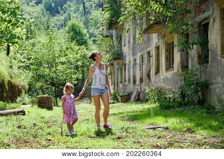 Young mother with little daughter walking in dead city with abandoned buildings and ruins, rear view