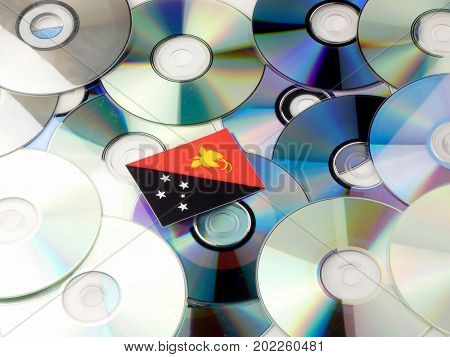 Papua New Guinea Flag On Top Of Cd And Dvd Pile Isolated On White