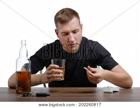 A drunk man is holding and looking at a big glass full of whiskey and a cigarette, isolated on a white background. A boozed guy with an alcoholic drink and pack of cigarettes on a wooden table.