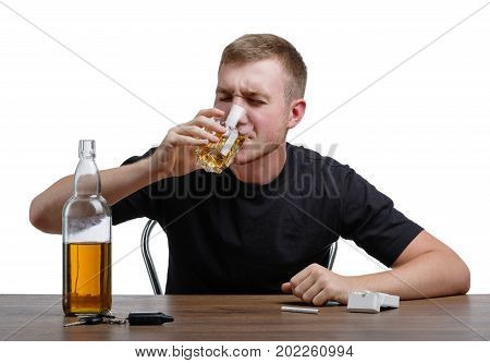 A yound despaired guy wearing a black T-shirt is drinking a light brown scotch or whiskey, isolated on a white background. A  lonely sad male with a bottle, a glass, and cigarettes at a table.