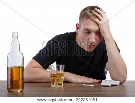 A boozed male sitting next to a bottle full of a light brown liquor or whiskey on a table, isolated on a white background. A big bottle full of alcohol beverage and a pack of cigarettes on a table.