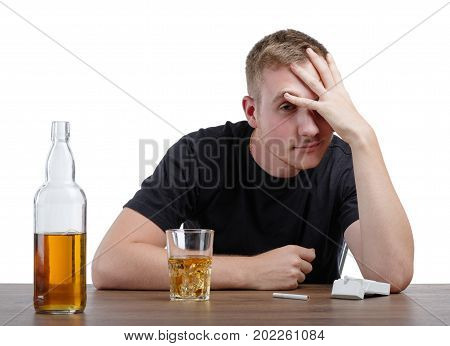 An alcoholic with a light brown liquor or whiskey in a glass and in a bottle, isolated on a white background. A big bottle full of alcohol beverage and a pack of cigarettes on a table. Copy space.