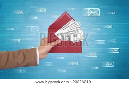 Female hand holding coloured and white envelope with blue background and message symbols around