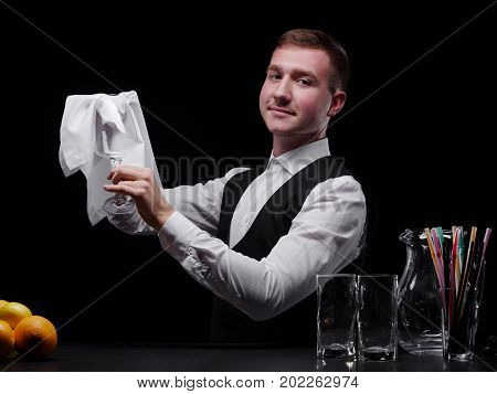 Portrait of a professional nightclub barman cleaning a fancy glass next to fruits, straws and empty glasses on the black background. A young barkeeper with light brown hair, wearing a classic suit.