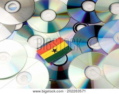 Ghanaian Flag On Top Of Cd And Dvd Pile Isolated On White