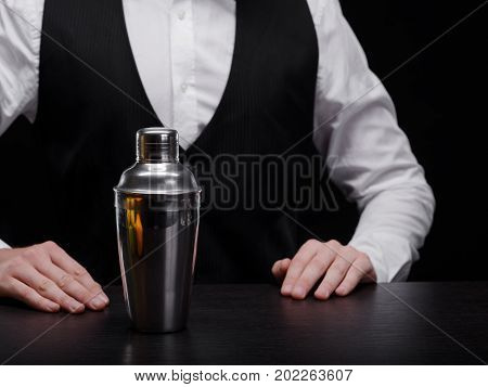 Elegant club bartender in a professional suit with a metal empty shaker for mixes, shakes and cocktails on the black background. Close-up of a shaker and barkeeper in a black jacket and white shirt.