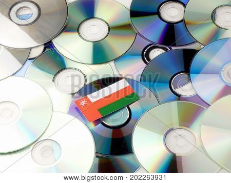 Omani Flag On Top Of Cd And Dvd Pile Isolated On White