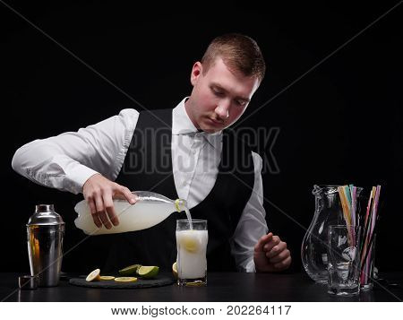 A stylish, modern bartender behind a bar counter with glasses, shaker, straws and cut citruses. A barman pouring Schweppes in a glass. Bartender making a shake or mix on the black background.
