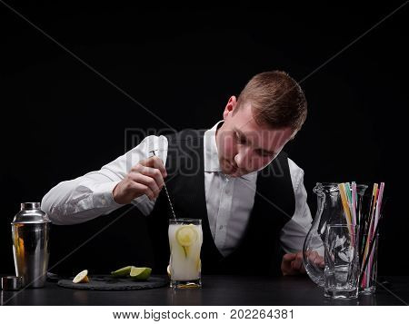 A professional, modern bartender behind a bar counter with glasses, shaker, straws and cut citruses. A barman mixing a cocktail in a glass. Bartender making a shake or mix on the black background.