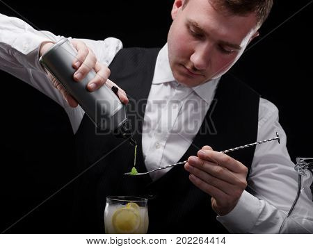An elegant, classic bartender with a professional equipment for mixes on a black background. A young barman pouring juice on a long spoon and a glass of alcoholic fruity beverage.