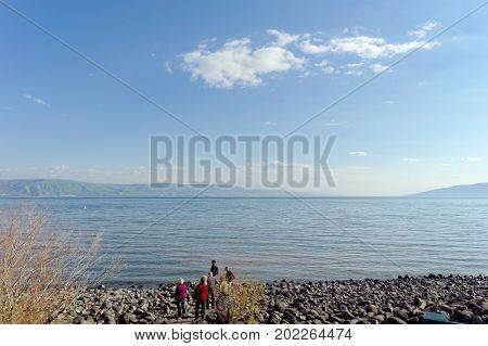 View of the shores of the Sea of Galilee near the Capernaum. A group of pilgrims stand near the water on the pebbles.