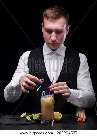 A confident male bartender in traditional white shirt and black jacket behind a bar counter. Barmen with a colorful shake with straws and sliced fruits on the black background. Club, pub, bar concept.