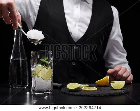 Close-up picture of a barman pouring crushed white ice in a glass on the black background. A club bartender adding ice to a refreshing, cold shake with alcohol, limes and aromatic mint.