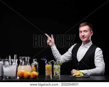 A successful male bartender in a classic suit pointing at something on the black background. Beautiful barman behind a bar counter with glasses, jars, citrus fruits and cocktails. Copy space.
