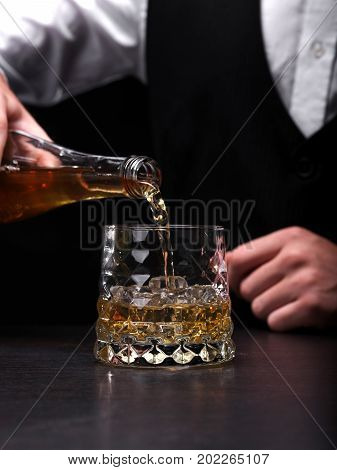 Close-up of a barman pouring liquor or rum in a transparent fancy glass standing on a bar counter. Expensive, traditional, refreshing, classic alcoholic whiskey on the black background.