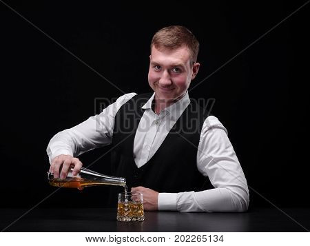 Portrait of a barman pouring liquor or rum in a transparent fancy glass standing on a bar counter. Expensive, traditional, refreshing, classic alcoholic whiskey on the black background.