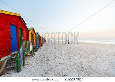 Kids playing at famous colorful huts of Muizenberg beach near Cape Town in South Africa