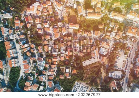 Old European city with red tiled roofs of houses, top view.