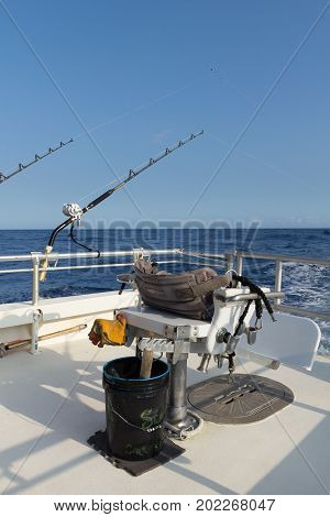 Fighting chair and bucket set up and with fishing gear on offshore boat in Pacific Ocean.