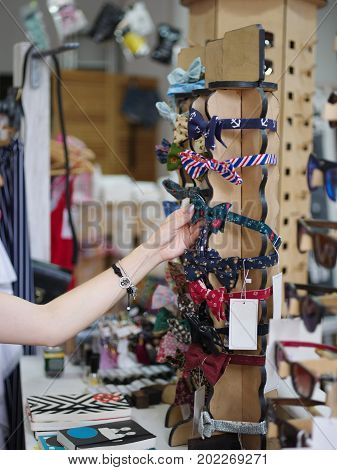 Close-up of a tender woman's hand taking cute, colorful hoops for hair on a blurred shop background. Gil choosing hair accessories in a store. A stand with many pretty bright hoops for hair.