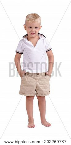 A full-length portrait of a small barefooted boy in a summer clothes. A cheerful cute child standing isolated on a white background. A blond smiling kid. Childhood, hapiness concept.
