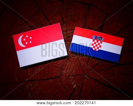 Singaporean Flag With Croatian Flag On A Tree Stump Isolated