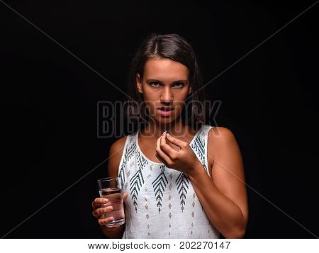 A close-up picture of a student girl taking prescripted antidepressants on the black background. Casual young female with antibiotics or aspirin and fresh water. A sad brunette lady taking medicine.