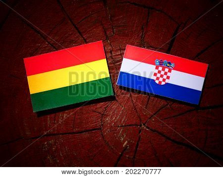Bolivian Flag With Croatian Flag On A Tree Stump Isolated