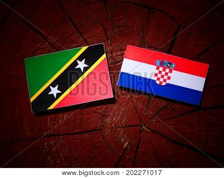 Saint Kitts And Nevis Flag With Croatian Flag On A Tree Stump Isolated
