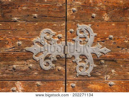 Old iron hinge on a worn wooden door