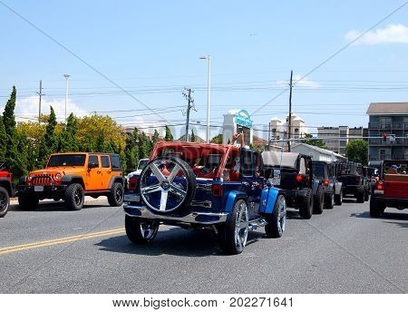 OCEAN CITY MD - AUGUST 26 2017: A pair of hands holding a cellphone takes a mobile photo from out of the top of an open vintage jeep waiting at a traffic signal in a line of jeeps at Jeep Week in Ocean City MD.