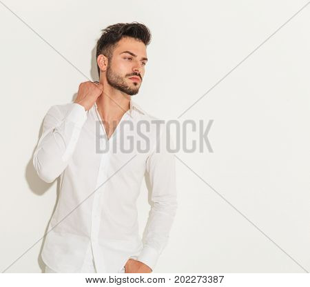 cool young man holds hand on his neck and looks to side away from the camera