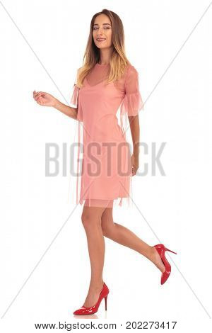 side view of a smiling woman with braces wearing dress and high heels shoes walking on white background, side view