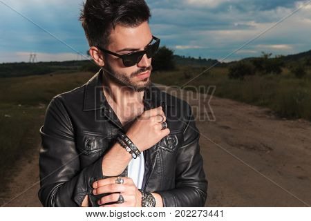 young man in leather jacket fixing his sleeve and looks to side in the middle of a country road