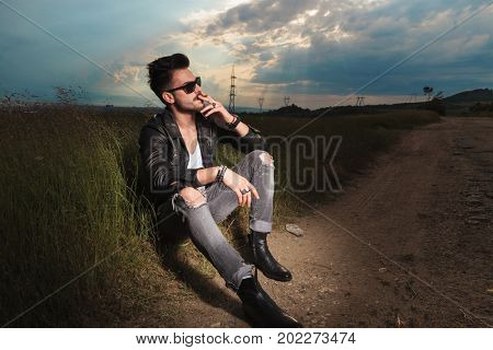 side view of a seated man, smoking a cigarette on the side of the road