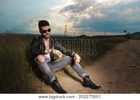fashion model sits and smokes on the side of a country road againse dramatic summer sky