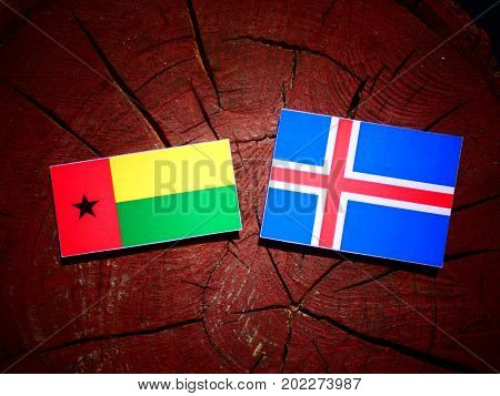 Guinea Bissau Flag With Icelandic Flag On A Tree Stump Isolated