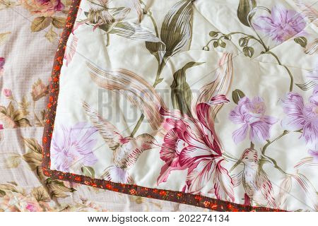 handmade, patchwork, quilting, sewing, home comfort concept - one light lemon coloured blanket with irises print and red tape cover another, pink one with roses