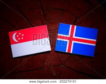 Singaporean Flag With Icelandic Flag On A Tree Stump Isolated