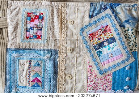 fashion, handcraft, patchwork, sewing concept - colorful textile fragment made of bright snippets with various prints, buttons, lace and embroidery for decorating