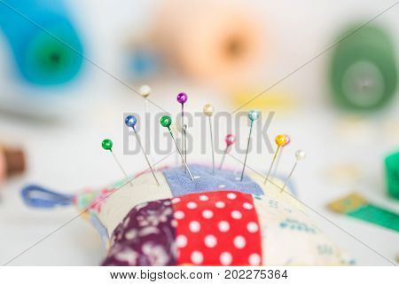 needlework, craft, sewing and tailoring concept - macro with colorful stitched pincushion and beautiful pins, measuring meter, pink, blue and green thread spools, white buttons, soap, selective focus poster