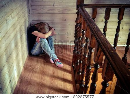 Depression. Sad girl teenager sits by the wall. Her head is on her knees, her face is covered with hands.