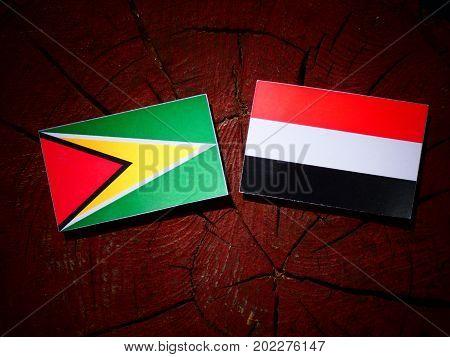 Guyana Flag With Yemeni Flag On A Tree Stump Isolated
