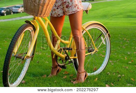 Beautiful Woman With Bike On Green Grass.