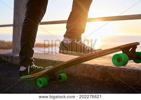 Longboarding along the ocean at sunset, anonymous feet on skateboard