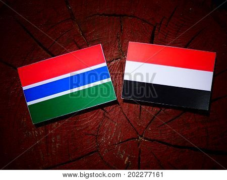 Gambia Flag With Yemeni Flag On A Tree Stump Isolated