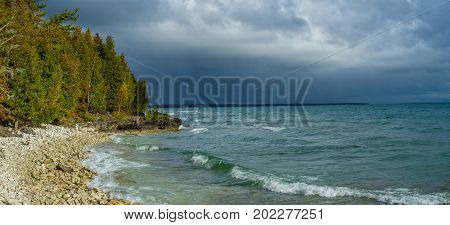stormy skies beyond a rocky outcropping in autumn at cave point county park door county wisconsin